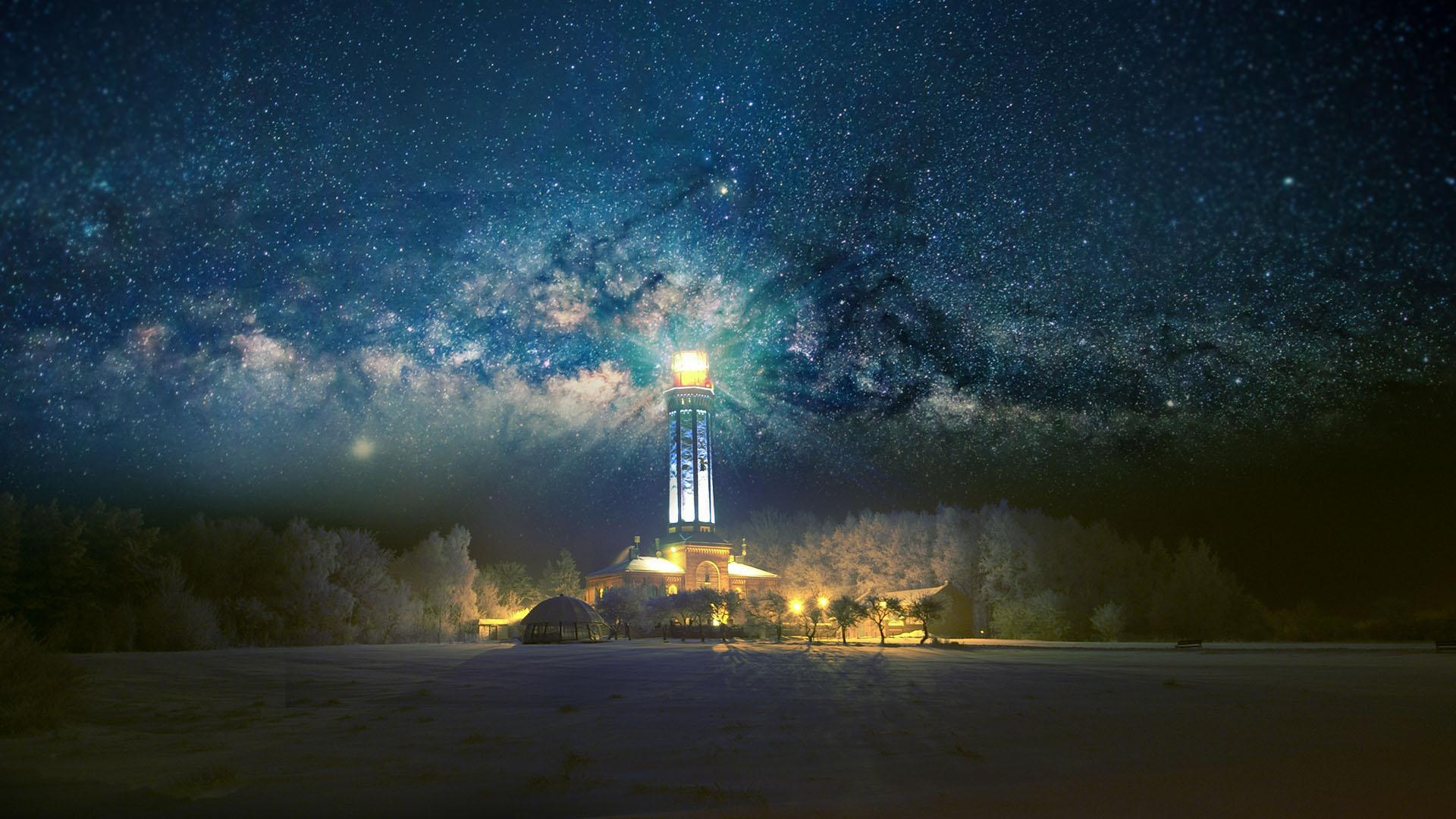 Latarnia morska w Niechorzu zimową porą. W tle gwieździste niebo.